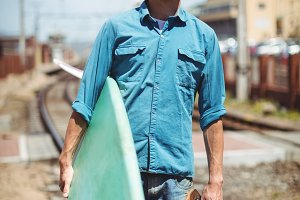 Man carrying skateboard and surfboard