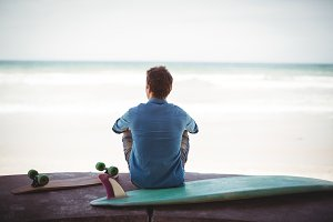 Man with skateboard and surfboard sitting on beach