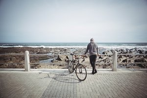 Man standing with the bicycle near the seashore