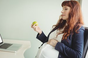 Pregnant businesswoman holding an apple