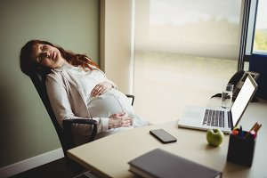 Pregnant businesswoman sleeping on chair