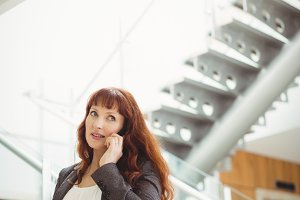 Pregnant businesswoman talking on mobile phone near stairs