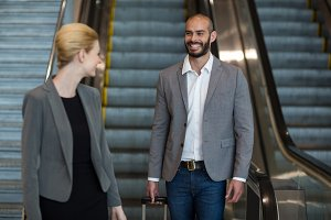 Smiling businesspeople with luggage moving down on escalator