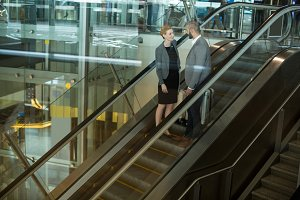 Businesspeople interacting with each other while going up on escalator