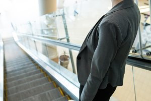 Businesswoman with luggage moving down on escalator