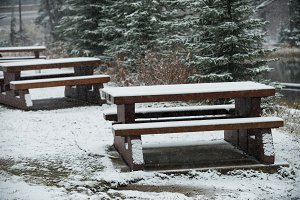 Snow-covered benches beside the lake