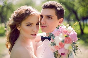 bride and groom with a bouquet of red peonies in the summer
