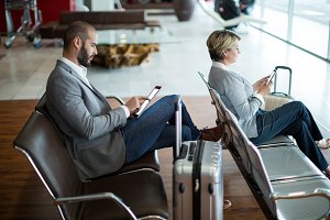 Businesspeople using digital tablet and mobile phone in waiting area
