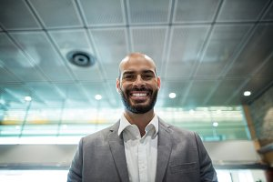 Portrait of smiling businessman standing in waiting area