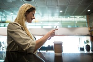 Smiling woman using mobile phone in waiting area