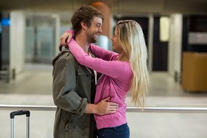 Cheerful couple embracing each other in waiting area