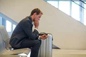 Businessman using mobile phone in waiting area