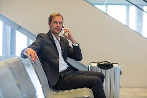 Businessman talking on mobile phone in waiting area
