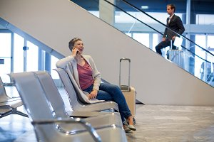 Smiling woman talking on mobile phone in waiting area