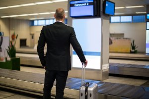 Rear view of businessman standing with luggage at waiting area
