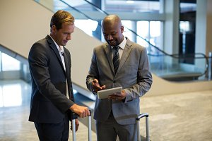 Business people with luggage bag using digital tablet