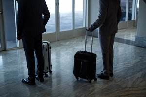 Business people with luggage standing at waiting area