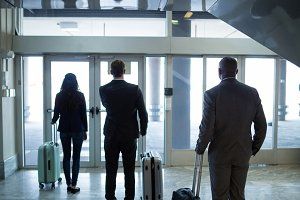 Business people with luggage standing at waiting area in airport