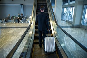 Businessman on escalator at airport