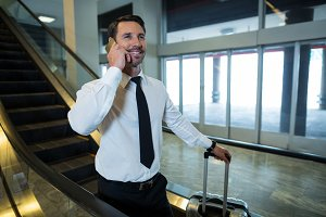 Businessman on escalator talking on mobile phone