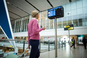 Rear view of female commuter standing with luggage at waiting area