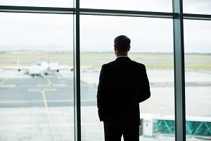 Rear view of businessman looking through window in waiting area
