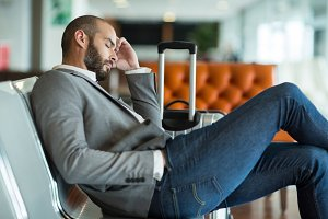 Businessman sleeping on chair in waiting area