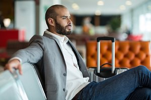 Thoughtful businessman sitting on chair in waiting area