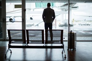 Rear view of businessman with luggage looking through glass window