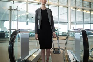 Businesswoman near escalator with luggage