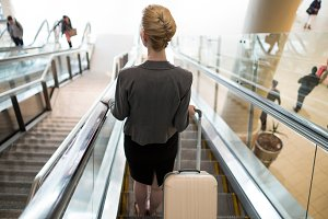 Businesswoman standing on escalator with luggage