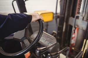Hands of mechanic driving forklift