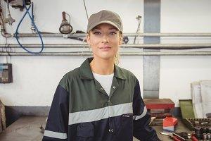 Portrait of beautiful female mechanic in garage
