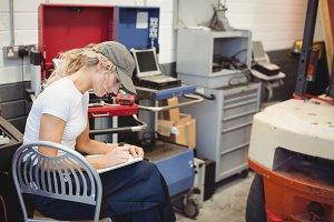 Female mechanic writing on notebook