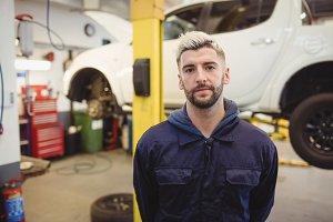 Portrait of young mechanic standing in garage