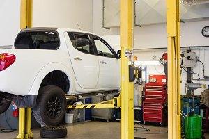 Car on hydraulic lift in garage