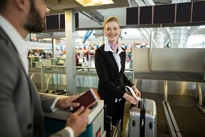 Airline check-in attendant sticking tag to the luggage of commuter