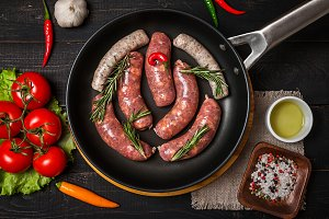 Raw sausages in a frying pan