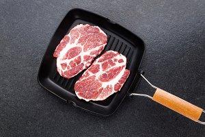 raw steak in a frying pan