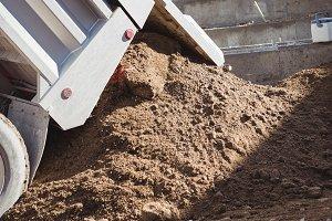 Dumper unloading mud at construction site