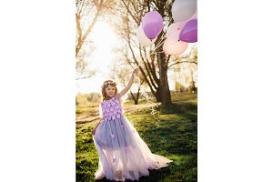 Girl in a beautiful purple dress playing with balloons in the park