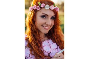 Young red-haired woman with a wreath of flowers in the rays of sunset