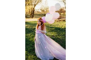 Red-haired woman in purple dress walking in park with balloons in hand, at sunset