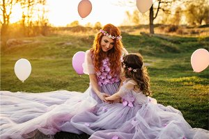 Young red-haired mother with her daughter resting on nature in the sun