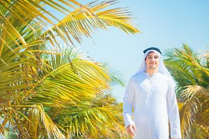 Arabian Man Walking Among Palm Trees