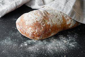 Close-up of Italian ciabatta bread in flour on a black table