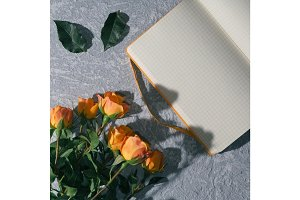 Open yellow notebook with a blank page and a bouquet of yellow roses on a blue table under the morning light. Copy space.