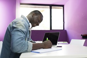 African man learning at classroom.