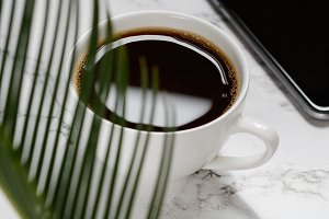 Freshly brewed black coffee, smartphone and a palm leaf on a white marble table.