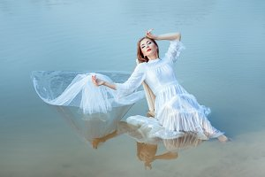 Girl sits on the lake and is reflected surface water.